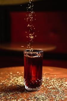 バーで、木製のテーブルの上で、氷の槍とコリンズハイボールグラスでカクテル。松葉でカクテルを振りかける。