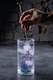 회색 표면에 흰색 꽃으로 장식 된 블루 리큐어와 얼음이 들어간 키가 큰 잔에 담긴 칵테일. 바텐더는 칵테일을 혼합합니다.