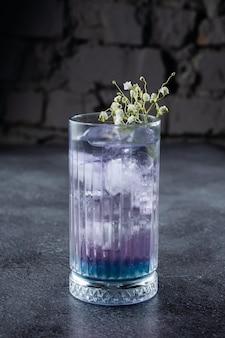 회색 표면에 흰색 꽃으로 장식 된 블루 리큐어와 얼음이 들어간 키가 큰 잔에 담긴 칵테일.