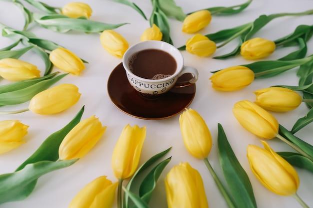 화이트 튤립의 프레임에 커피 컵.