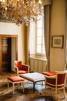 シックなシャンデリアの下に窓とカーテンのある部屋にアームチェア2脚とスツールが置かれたコーヒーテーブル