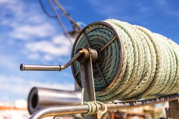 Катушка толстой веревки на рыбацкой лодке. алвор португалия.