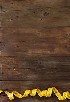 茶色の木製のテーブルトップビューにコイル状の黄色の測定テープ