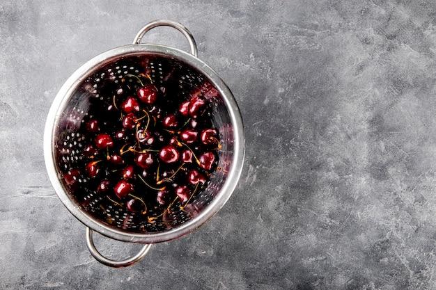 테이블에 회색 배경 여름 딸기에 소쿠리 익은 체리