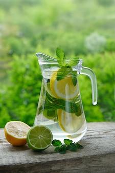 レモン、ライム、ミントをガラスの水差しで作った冷たい飲み物