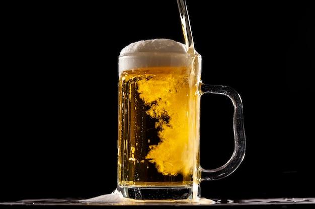 黒い壁の前で冷たい新鮮なビール
