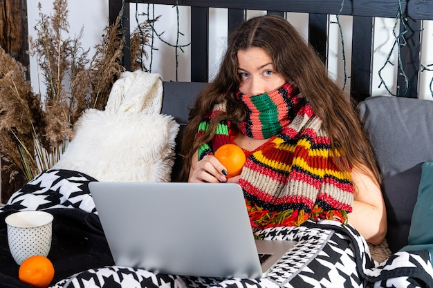 首に暖かいスカーフを巻いた冷たい若い女性がベッドに座って、ラップトップでリモートで作業しています