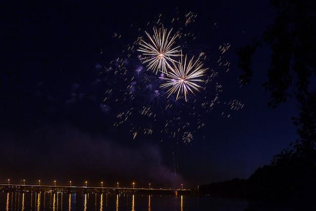 夜に爆発する花火のコラージュ。ライトスポットで飾られています。休日の背景に適しています。