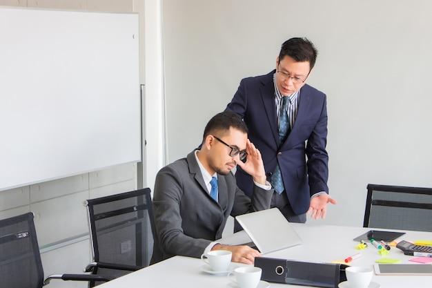 同僚は、オフィスで間違って働いている主人から彼を非難された後、悲しそうな顔で友人を励ましています。アジアビジネスのコンセプト