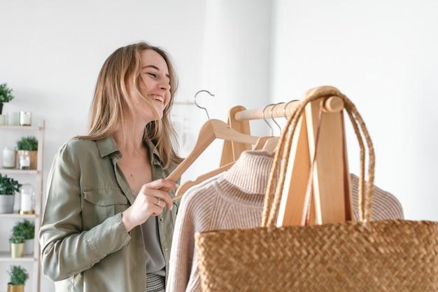 드레싱 룸에 옷걸이에 걸려있는 베이지 색 톤의 옷 컬렉션. 천연 소재. 여자는 세련된 옷을 선택합니다.