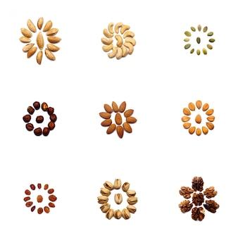 Коллекция орехов из миндаля, грецких орехов, фундука, фисташек, кешью лежит в форме круга или солнца на изолированной белой стене. различные орехи