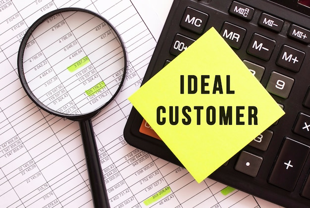 На калькуляторе лежит цветная наклейка с текстом идеальный клиент. финансовая концепция.