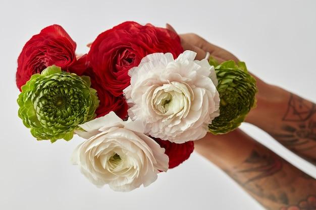 다양한 꽃의 화려한 꽃다발이 회색 배경에 문신을 한 소녀를 들고 있습니다. 축제 인사말 카드의 개념은 발렌타인 데이 또는 어머니의 날입니다