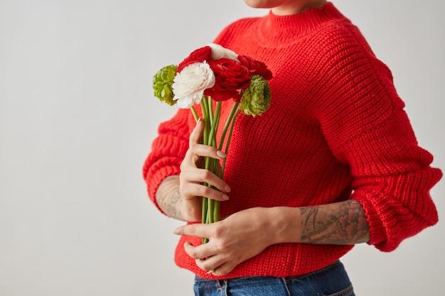 흰색, 빨간색 및 녹색 꽃의 화려한 꽃다발 라넌큘러스는 복사 공간이 있는 회색 배경에 문신을 한 소녀가 들고 있습니다. 봄 시간입니다. 어머니의 날