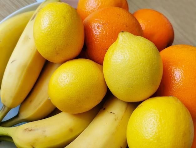 Красочная композиция из свежих фруктов на деревянном столе. ингредиенты: бананы, апельсины и лимоны.