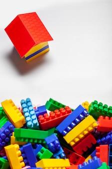 カラフルなコンストラクターが白い表面にクローズアップを設定しました。子供のための教育ゲーム。プラスチック製の子供用デザイナーキューブ。家を建てる、建物の概念。フラットレイ、上面図