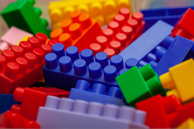 家の床にあるカラフルなコンストラクターセットのクローズアップ。子供のための教育ゲーム。プラスチック製の子供用デザイナーキューブ、セレクティブフォーカス。