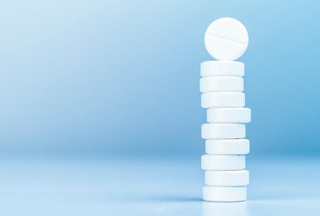 Столбик белых таблеток на столе