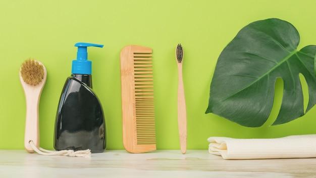 緑の背景に櫛、液体石鹸、歯ブラシ、タオル。外観ケア用メンズアクセサリー。