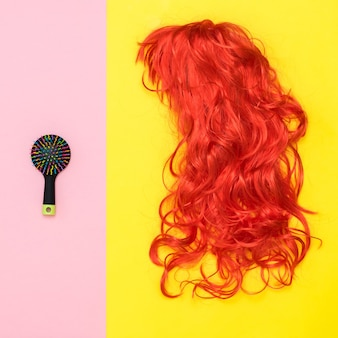 분홍색 배경에 빗과 노란색 배경에 주황색 가발. 생활 양식. 스타일을 만드는 액세서리.
