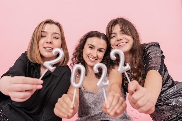 ピンクの背景に陽気なガールフレンドの会社は、番号2022、新年のお祝い、クリスマスパーティーを開催します。