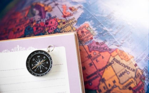地図の背景のノートに配置されたコンパス旅行地理ナビゲーションの概念の背景