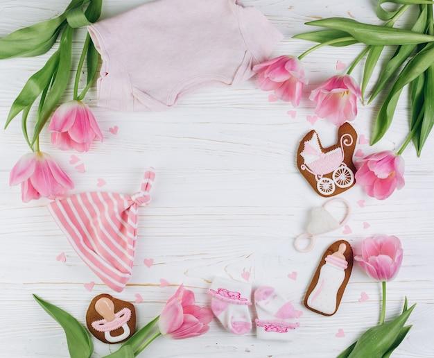 服、ピンクのチューリップと木製の白い背景に新生児のための組成物。