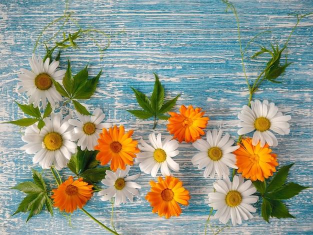 青い木製の背景に花の構成