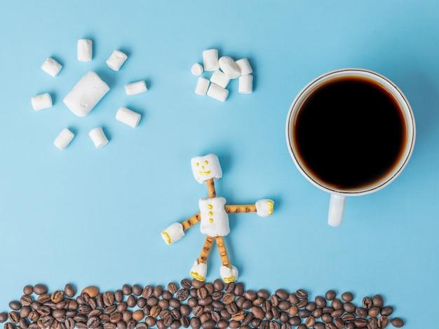 青い背景にマシュマロとコーヒーの組成物。お菓子のコラージュ。フラットレイ。