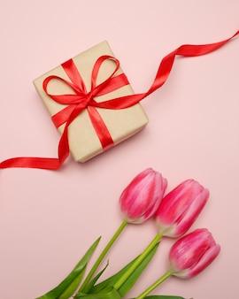 튤립과 분홍색 배경에 빨간 리본으로 묶인 상자에 선물 구성.