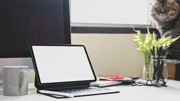 Планшетный компьютер с чехлом для клавиатуры ставится на белый рабочий стол в домашнем офисе