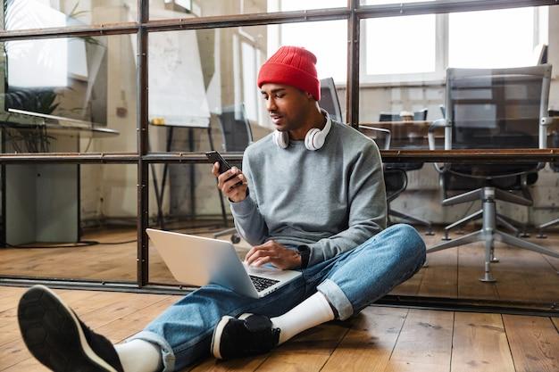 Сосредоточенный африканский молодой человек сидит в помещении на полу, используя портативный компьютер и мобильный телефон.