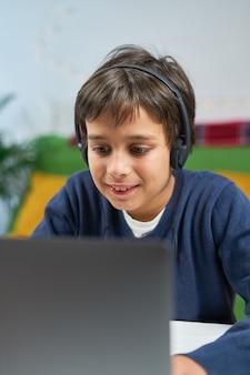 Сосредоточенный мальчик, использующий ноутбук, в наушниках, сидит один дома