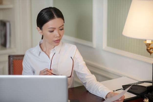 Концентрированная деловая женщина, изучающая важный документ