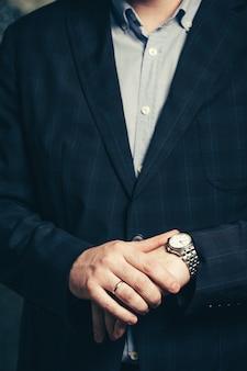 集中しているビジネスマンが時間を見ています。腕時計を持つ男。