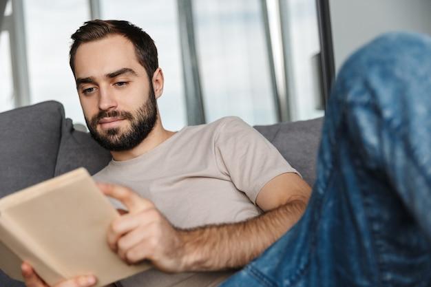 Концентрированный серьезный молодой красавец в помещении дома на софе, читая книгу.