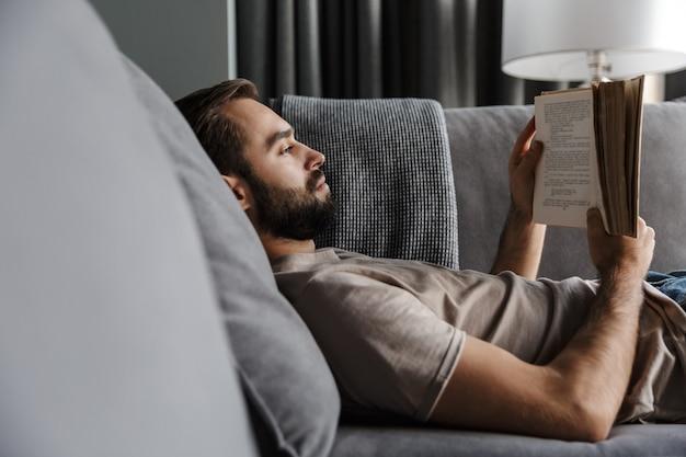 Концентрированный молодой красавец в помещении дома на софе, читая книгу.