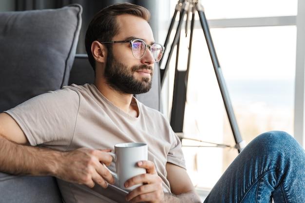 コーヒーを飲みながら自宅の屋内で眼鏡をかけた集中した若い男。