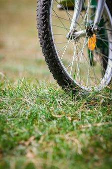 Велосипедное колесо concept на траве в парке путешествия
