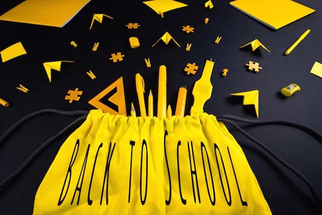 学校に戻って主題に関するコンセプト。黒い背景に学生の黄色の文房具。