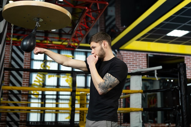 Концептуальный портрет жестокого татуированного боксера, который тренируется на ринге и попадает в боксерскую грушу.