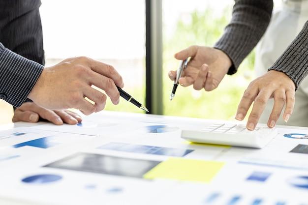 幹部やマーケターが販売文書を見て分析、マーケティングの計画、販売促進を行う会議室で、ブレインストーミングを行っています。販売管理の概念。