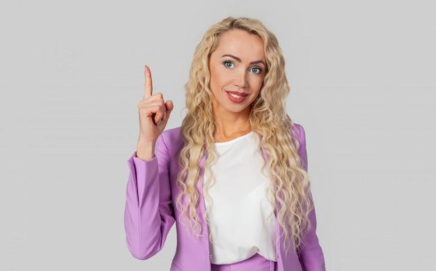 自信を持って横暴な女性は上を指して方向を示し、指でナンバーワンを示します。たとえば、良い製品について話している、笑顔でカメラを見て喜んでいるようなアドバイスです。