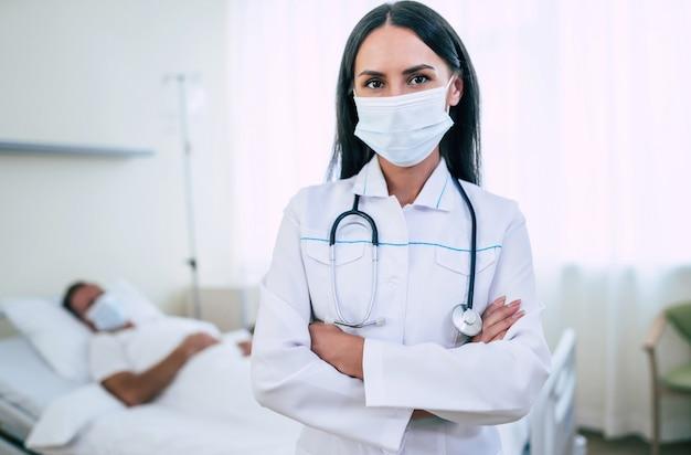 안전 의료 마스크에 자신감이있는 의사 여자가 병동에 누워있는 동안 마스크에 성숙한 환자를 검사하고 있습니다.