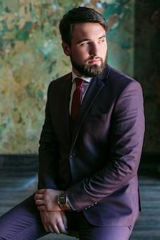 素敵なスーツを着てスタジオで緑の背景の前に立っている自信を持ってエレガントなハンサムな若い男。ビジネスマン