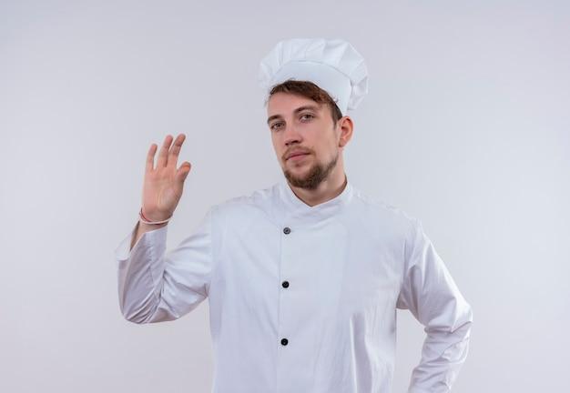 Уверенный в себе молодой бородатый шеф-повар в белой униформе и шляпе показывает вкусный жест пальцами на белой стене