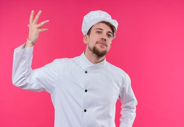 Уверенный в себе молодой бородатый шеф-повар в белой форме поднимает руку вверх, глядя на розовую стену