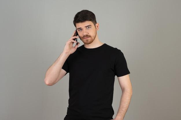 Уверенный в себе молодой парень держит телефон и смотрит в камеру на сером. Premium Фотографии