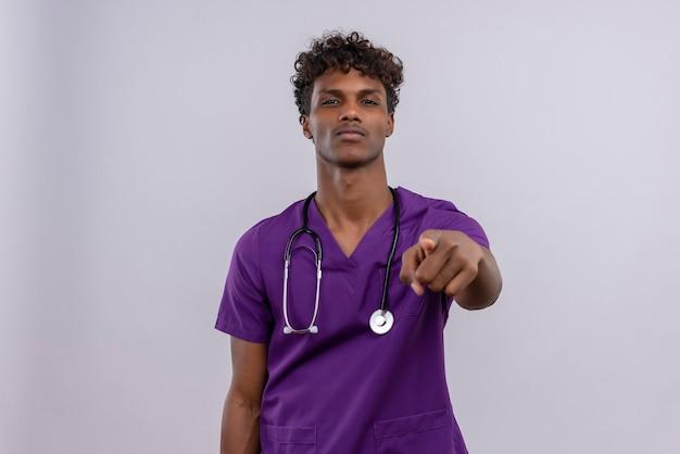 人差し指でカメラを指して聴診器で紫の制服を着た巻き毛の自信を持って若いハンサムな浅黒い医者