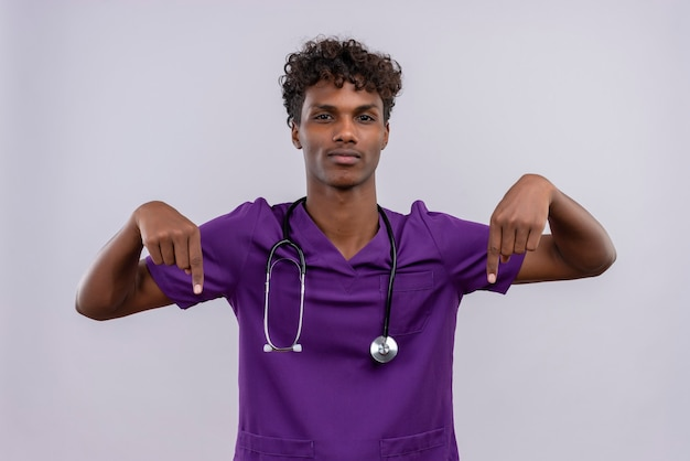 聴診器で人差し指で上向きに紫の制服を着た巻き毛の自信を持って若いハンサムな浅黒い医者